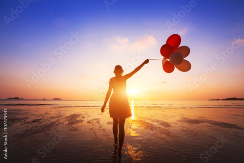 Obraz happiness concept, positive emotions, happy girl with multicolored balloons enjoying summer beach at sunset - fototapety do salonu