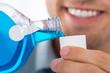 Leinwandbild Motiv Man Pouring Bottle Of Mouthwash Into Cap