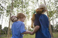 Caucasian Brothers Carrying Stuffed Animals Outdoors