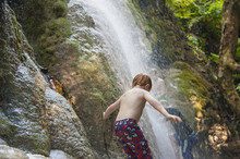 Caucasian Boy Playing In Jungle Waterfall