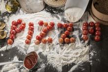 Scritta Pizza Con I Pomodorini Rossi Con Tutti Gli Ingredienti Attorno Quali Farina, Sugo, Olio, Funghi- Sfondo Tavolo In Legno