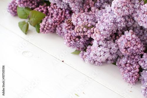 Fototapeta tło- bukiet kwiatów bzu lerzący na deskach, tabliczka z napisem i napis love obraz