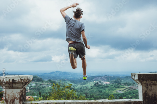 Fotografie, Obraz  Hipster traveler jumping against the mountains, Bali