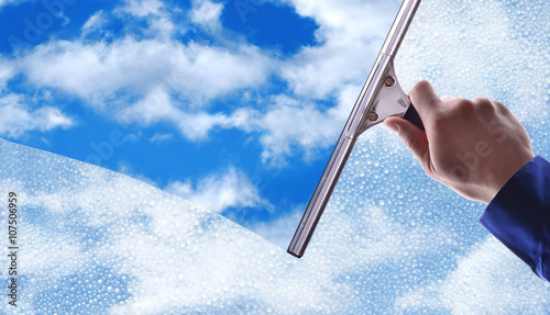 Fotografie, Obraz  Employee cleaning a glass with rain drops and blue sky