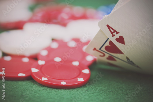 фотография  Poker chips and cards on a green table
