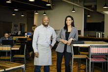 Waiter And Businesswoman Smiling In Cafe