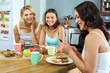 Friends using mobile phones while having breakfast at home