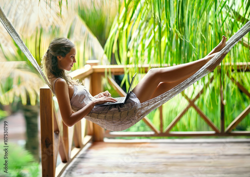 Obraz na plátně Young woman lying in a hammock with laptop