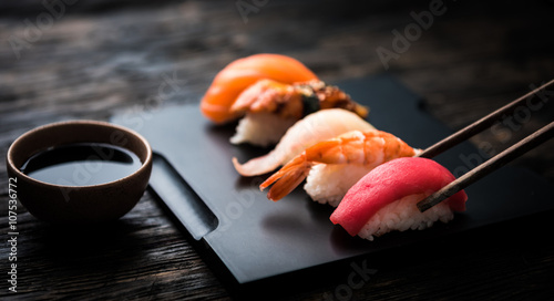 Photo Stands Sushi bar close up of sashimi sushi set with chopsticks and soy