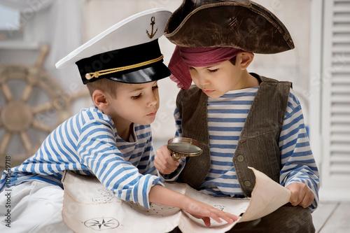 Plakat Chłopcy przebrani za piratów i czytają mapę podróży