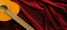 Classical Nylon Guitar Lying On Red Velvet Textile, Artistic Instrument Presentation