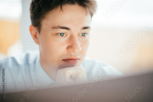 young man looking at a close-up monitor