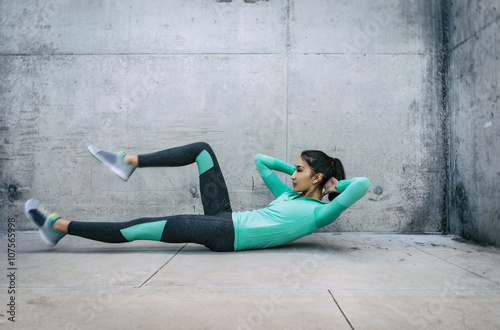 Fotografie, Obraz  Young woman performing core crunch exercise