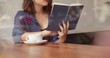 Girl Drinking Coffee and Reading Book in Cafe