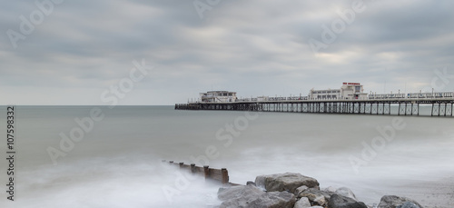 Aluminium Prints Dark grey Beautiful long exposure sunset landscape image of pier at sea in