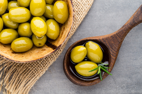 Fresh olives and gray background. Olives in bowl and spoon.