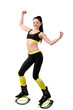 Smiling brunette girl in kangoo jumps shoes showing a muscles on