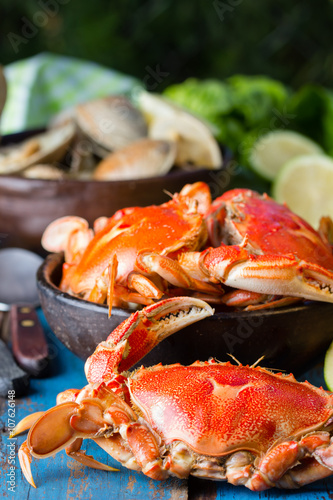 Fotobehang Schaaldieren Seafood. Crsbs in clay bowl and shellfish soup of clams on wooden blue background. Mariscal or paila marina
