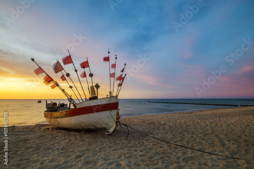 Stampa su Tela fishing boat on the sea shore in the light of the setting sun