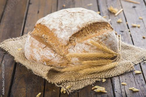 fototapeta na lodówkę Hogaza de pan de trigo y centeno sobre una arpillera en la mesa de la cocina decorada con espigas de cereales