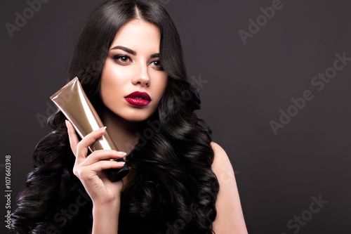 Poster  Beautiful brunette model: curls, classic makeup and red lips with a bottle of hair products