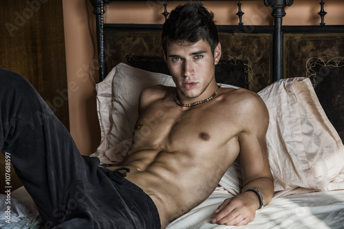 obraz dibond Shirtless sexy male model lying alone on his bed