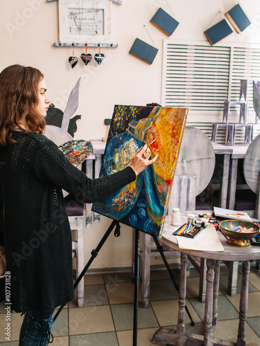 hipster artist paints a colorful abstract painting closeup of