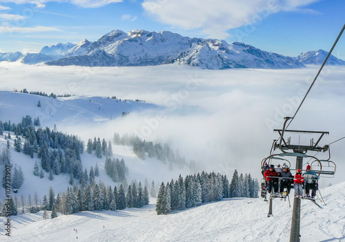 Fotografie, Obraz  Alpine ski slope mountain winter panorama with ski lift,skiers and snow covered forest