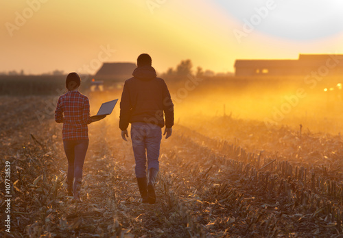 Obraz na płótnie Farmers walking on field during baling