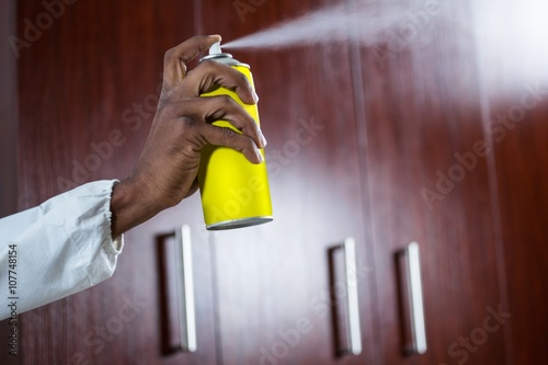 Fotomural Hand spraying pesticide from a spray can