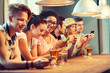 happy friends with smartphones and drinks at bar