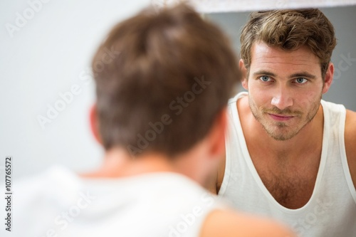 Fotografie, Obraz  Young man looking at himself in mirror