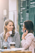 Two beautiful young woman sitting at cafe drinking coffee and having fun