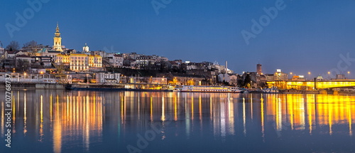 Old Belgrade panorama by night with Cathedral and Branko's bridge on Sava river and cityu lights water reflections