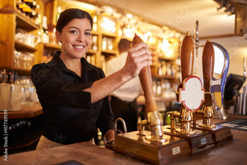 Photo A young woman working behind a bar looking to camera, horizontal