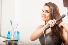 Woman Straightening Her Hair W...