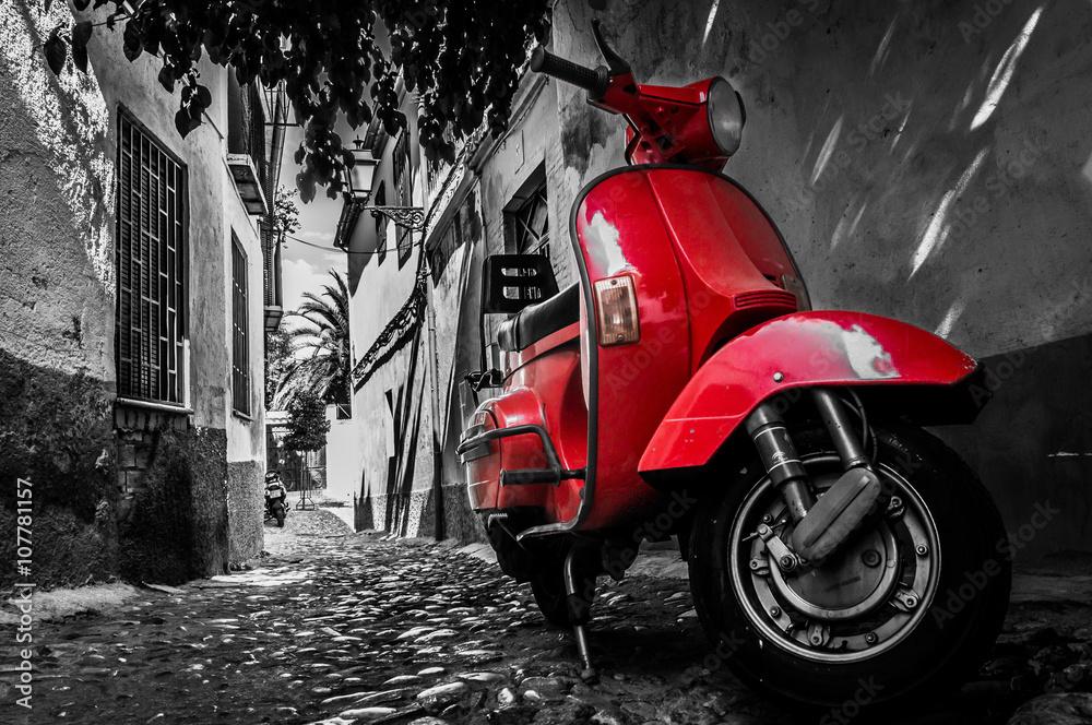 Fototapeta A red vespa scooter parked on a paved street