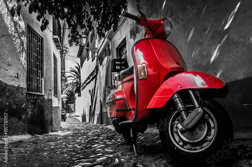 Fotografija  A red vespa scooter parked on a paved street