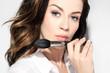Pędzel do konturowania twarzy. Piękna kobieta trzyma w dłoni profesjonalny pędzel do makijażu