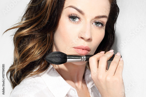 Fototapeta Pędzel do konturowania twarzy. Piękna kobieta trzyma w dłoni profesjonalny pędzel do makijażu obraz