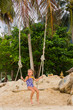 girl with two braids in a bathing suit on a swing on the beach