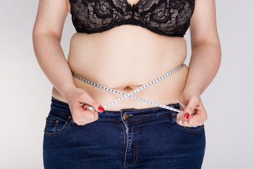 Overweight woman measuring her belly