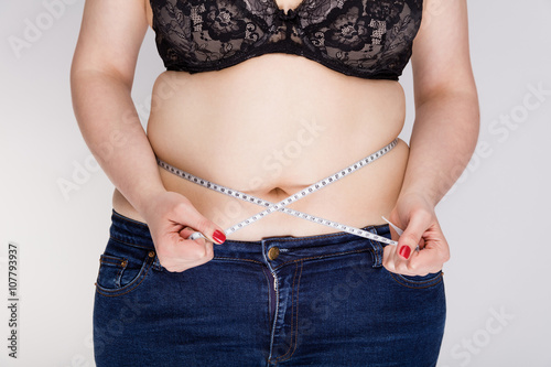 Fotografie, Obraz  Overweight woman measuring her belly