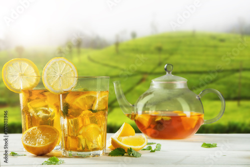 Staande foto Thee Cups of ice tea with plantation on background