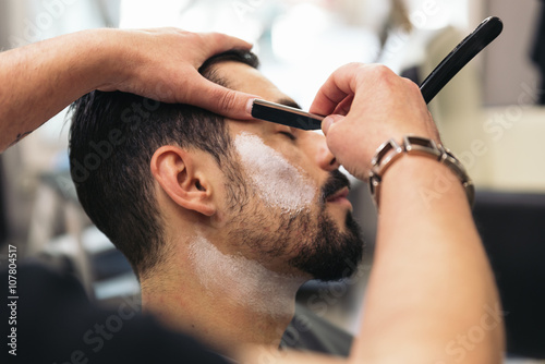 mata magnetyczna Bearded Man Getting Beard Haircut With A Razor By Barber