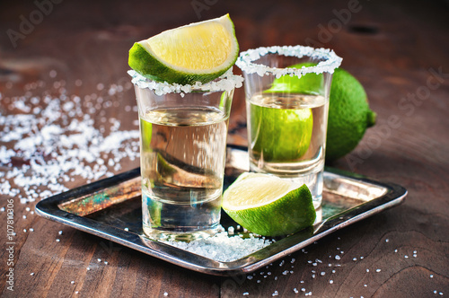 Fotografie, Obraz  Tequila gold, Mexican, alcohol in shot glasses, lime and salt, toned image, sele