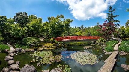 FototapetaКрасивый японский парк с прудом и красным мостом