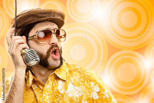 1970s vintage show man sing with hawaiian shirt and microphone on yellow backgro Wallpaper Mural