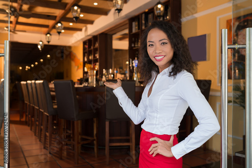 Photo Pretty smiling bar owner inviting you inside