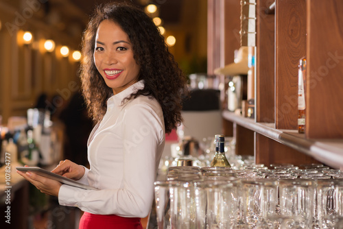 Fotografía  Smiling female pub owner with digital tablet looking at camera